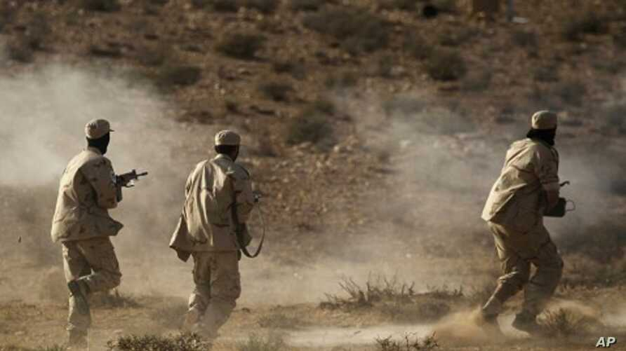 Libyan rebel fighters with the Tripoli Revolutionary Brigade take part in a live firing exercise near Nalut in western Libya, August 6, 2011.