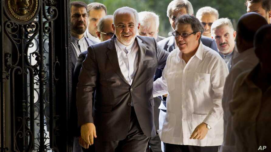 Iranian Foreign Minister Mohammad Javad Zarif, left, is welcomed by Cuban Foreign Minister Bruno Rodriguez, in Havana, Cuba, Aug. 22, 2016.