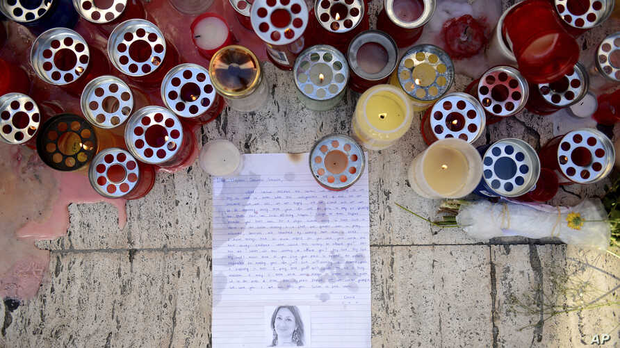 Candles, notes and paper cuttings lie next to the Love Monument in St. Julian, Malta, Oct. 17, 2017, the day after the killing of journalist Daphne Galizia.