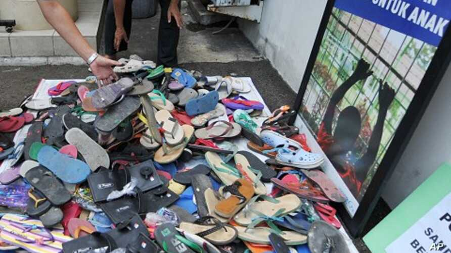 Officials from Indonesia's Child Protection Commission collect sandals sent to their office in Jakarta by outraged citizens as part of a campaign to support a boy who was beaten by police and faces five years in jail for stealing footwear, January 4,