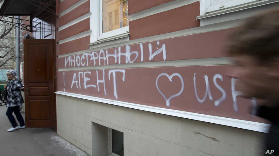 "FILE - A man passes by the office of ""Memorial"" rights group in Moscow, Russia. The building has the words ""Foreign Agent (Loves) USA"" spray-painted on its facade."
