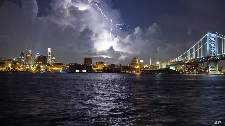 Lightning illuminates storm clouds over the Philadelphia skyline, Tuesday, August 16, seen from across the Delaware River in Camden, New Jersey.