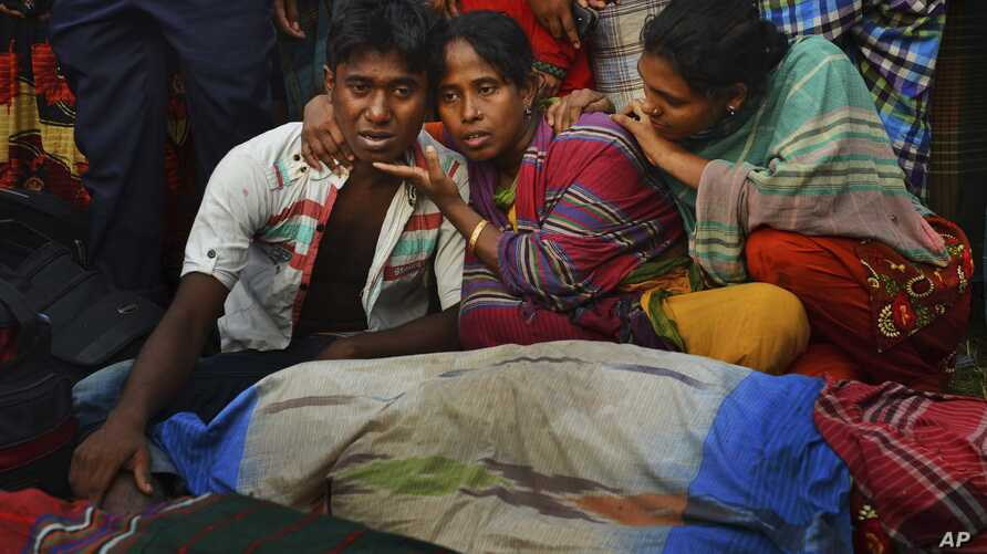 Relatives wail near bodies of victims on the banks of the River Meghna after a ferry capsized and sank in Munshiganj district, Bangladesh, May 15, 2014.