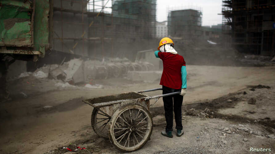 FILE - A female migrant construction worker is seen at a building site in Shanghai, China, July 2, 2013.