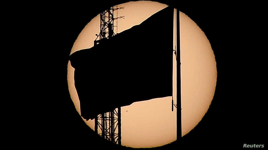 An American flag is silhouetted as the planet Mercury is seen, lower left quadrant, transiting across the face of the sun in Las Vegas, Nevada, May 9, 2016.