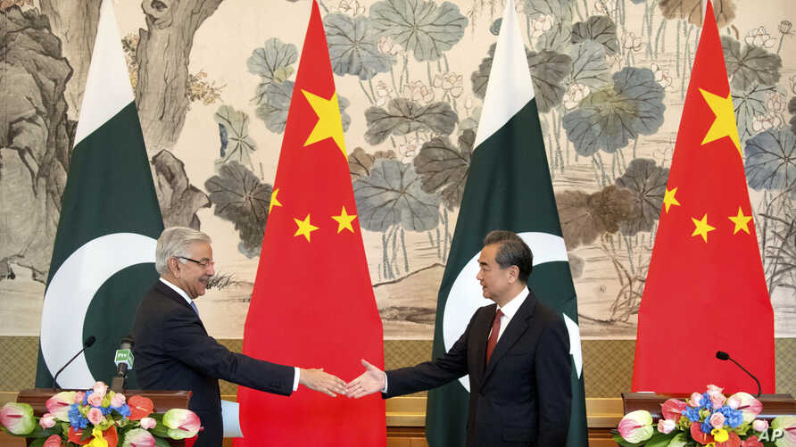 FILE - Pakistan's Foreign Minister Khawaja Muhammad Asif, left, and Chinese Foreign Minister Wang Yi reach to shake hands at the end of a joint press conference at the Diaoyutai State Guesthouse in Beijing, Friday, Sept. 8, 2017.