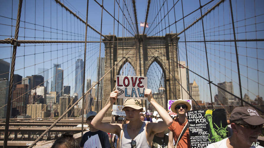 Activists carry signs across the Brooklyn Bridge during a rally to protest the Trump administration's immigration policies, June 30, 2018, in New York.