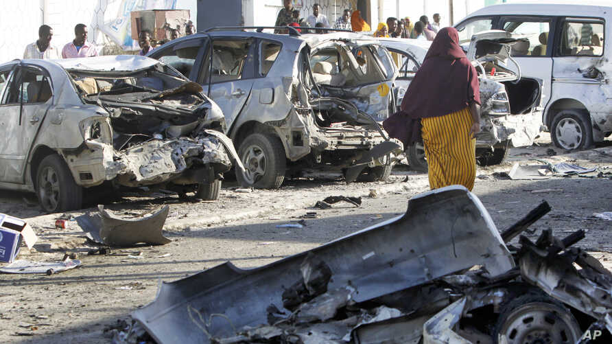 Somalis walk past the wreckage of vehicles outside a beachfront restaurant following an overnight attack of the restaurant in Mogadishu, Somalia, Jan. 22, 2016.