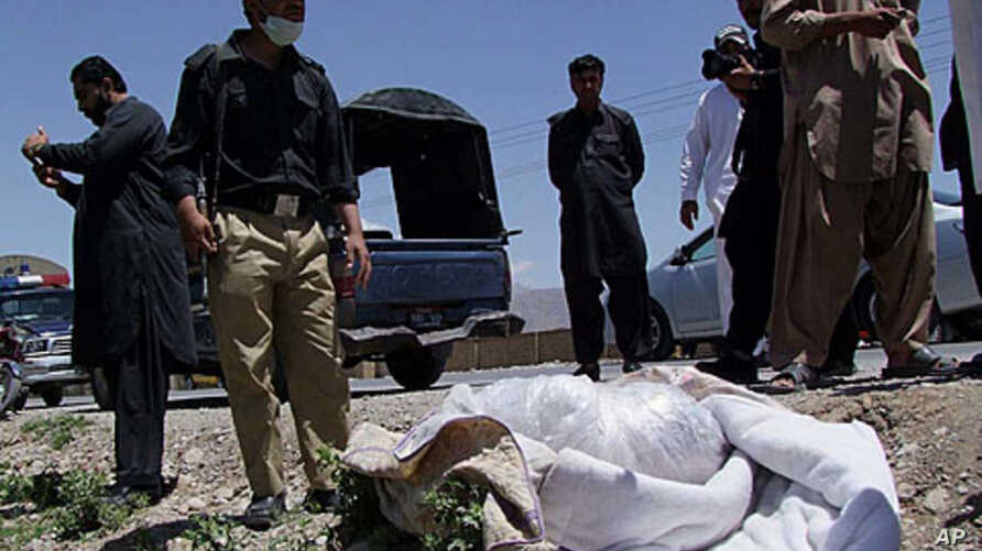 Pakistani security officials stand next to the covered body of British Red Cross physician Khalil Rasjed Dale in Quetta April 29, 2012.