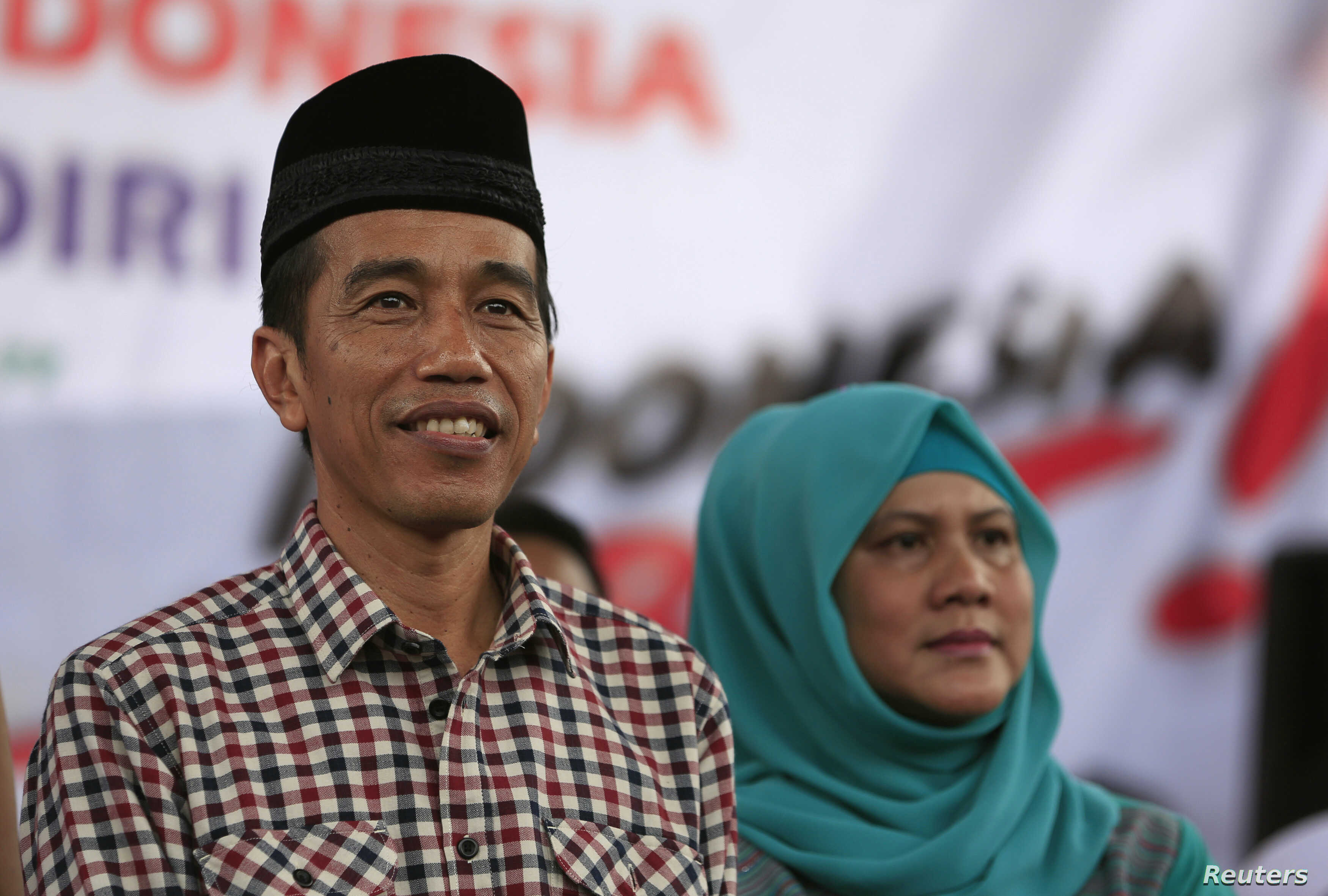 "FILE - Indonesian presidential candidate Joko ""Jokowi"" Widodo (L) looks on as he sits with his wife Iriana during a campaign rally in Majalengka, West Java province."