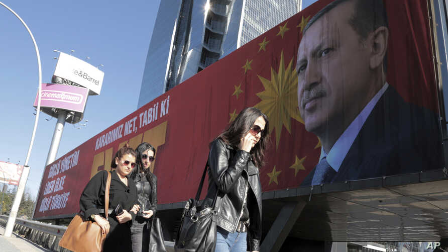 """People walk past a huge billboard with an image of Turkey's President Recep Tayyip Erdogan that reads """"Yes"""" in Turkish, in Ankara, Turkey, March 22, 2017. A referendum set for April 16 could boost Erdogan's powers."""