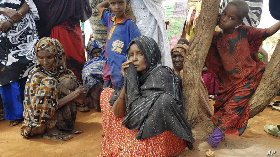 Ader Ali Yusuf, center, a mother of 12 who was displaced from her village due to the drought in Ethiopia, sits among a group of women as an international delegation visits the Warder town of Ethiopia's drought stricken area, June 9, 2017.