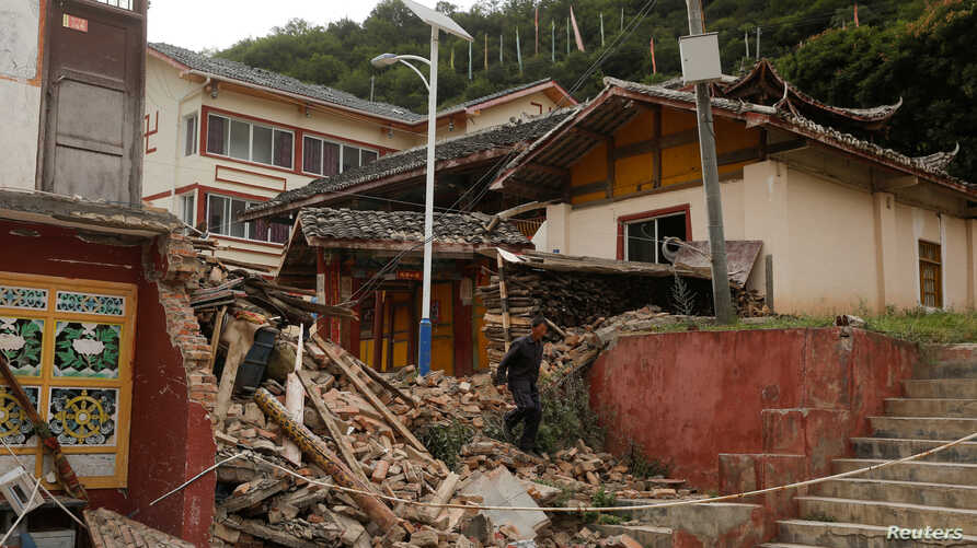 FILE - A man walks through the debris of a building that was damaged during an earthquake next to a temple compound in Jiuzhaigou, Sichuan province, China, Aug. 10, 2017.