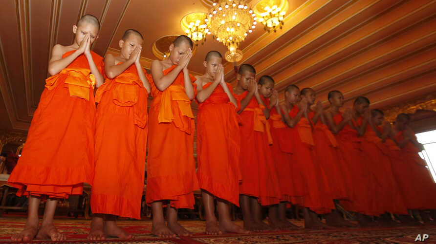 Members of Wild Boars soccer team pray during a ceremony marking the completion of their serving as novice Buddhist monks, following their dramatic rescue from a cave in Mae Sai district, Chiang Rai province, northern Thailand, Aug. 4, 2018.