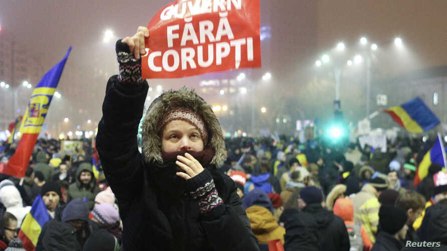 A woman holds up a sign that reads ' government without corruption' during a demonstration of thousands of Romanians against their government in Bucharest, Romania, Feb. 6, 2017.