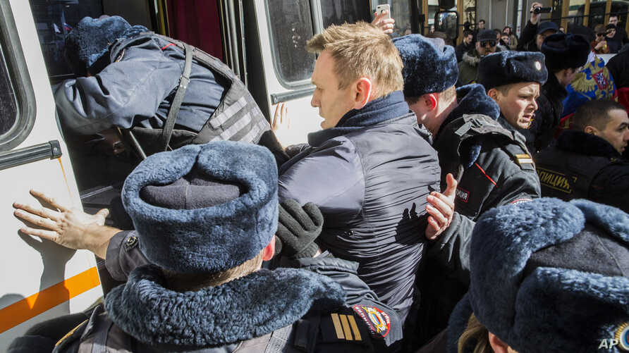 In this photo provided by Evgeny Feldman, Alexei Navalny is detained by police in downtown Moscow, March 26, 2017.