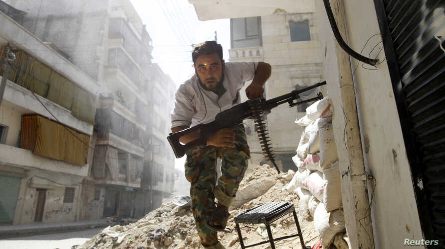A Free Syrian Army fighter takes cover during clashes with Syrian Army in the Salaheddine neighbourhood of central Aleppo in this August 7, 2012 file photo.