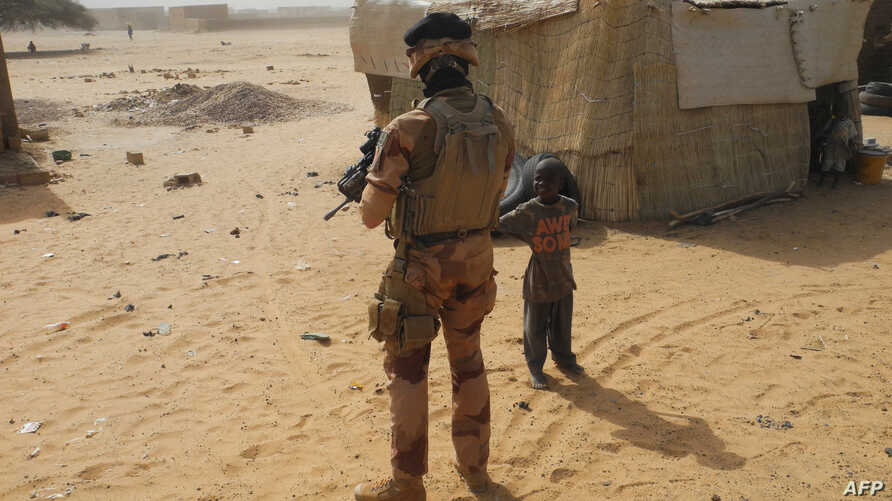 FILE - A soldier looks at a child as he patrols in Mali, March 25, 2019.