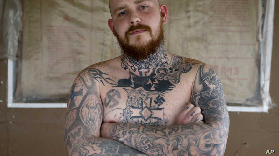 Shane Johnson displays some of his tattoos as he poses in his home in Tippecanoe, Indiana, Jan. 12, 2017. Johnson who was born into extremism is in the process of covering some of his racist tattoos with new ones and wears long sleeves to hide remnan