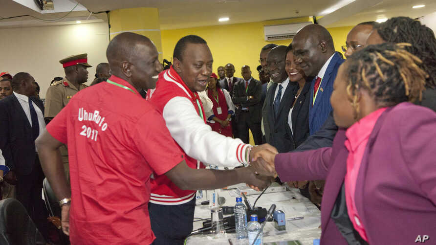 FILE - Jubilee Coalition presidential candidate Uhuru Kenyatta, 2nd left, accompanied by his running mate William Ruto, left, meets with Independent Electoral and Boundaries Commission (IEBC) members in Nairobi Kenya, May 29, 2017.