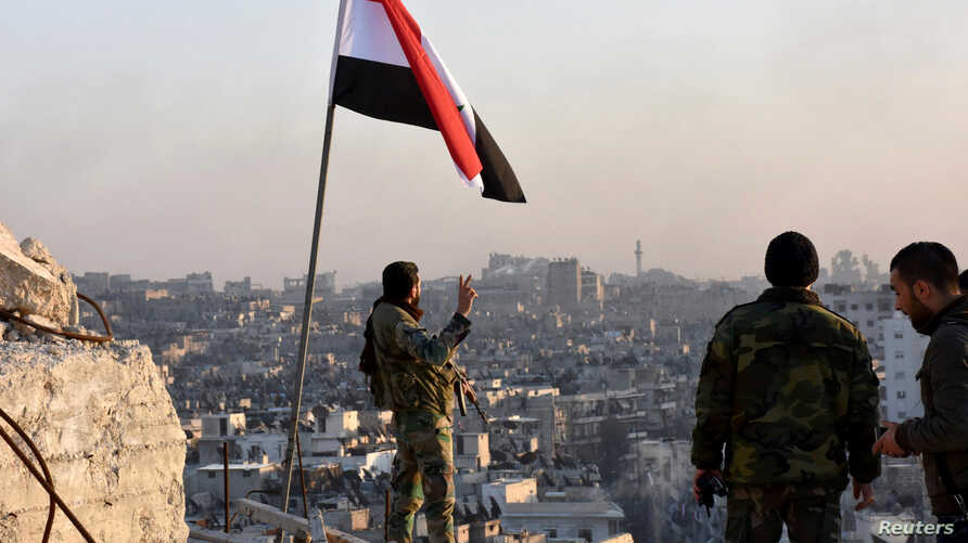 A Syrian government soldier gestures a v-sign under the Syrian national flag near a general view of eastern Aleppo after they took control of al-Sakhour neigborhood in Aleppo, Syria in this handout picture provided by SANA, Nov. 28, 2016.