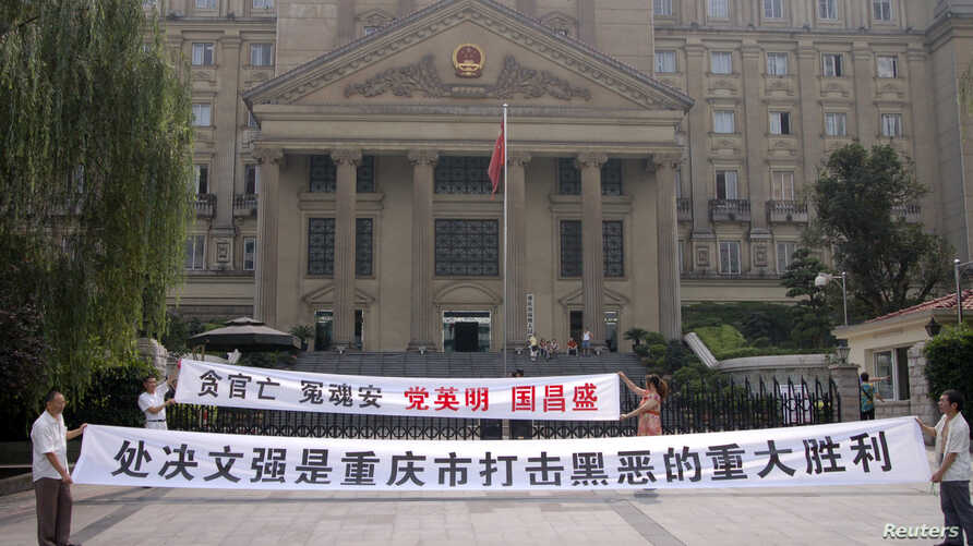 FILE - Residents hold banners outside the high court where Wen Qiang, the former municipal justice chief, was sentenced to death in Chongqing municipality.
