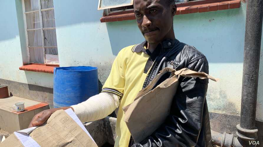 Adrian Munjere, who sustained fractures on his right hand during post-election clashes between security forces and protesters Aug. 1, displays his doctor's report in Harare, Oct. 17, 2018.