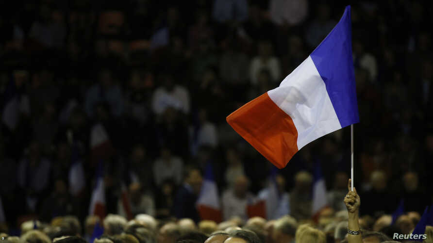"""A supporter raises a French flag as Nicolas Sarkozy, former head of the """"Les Republicains"""" political party and candidate for the French center-right presidential primary, attends a campaign rally in Nimes, France, Nov. 18, 2016."""