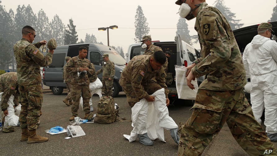 Members of the California Army National Guard don protective suits in preparation to search for human remains at the Camp Fire, Nov. 14, 2018, in Paradise, Calif.