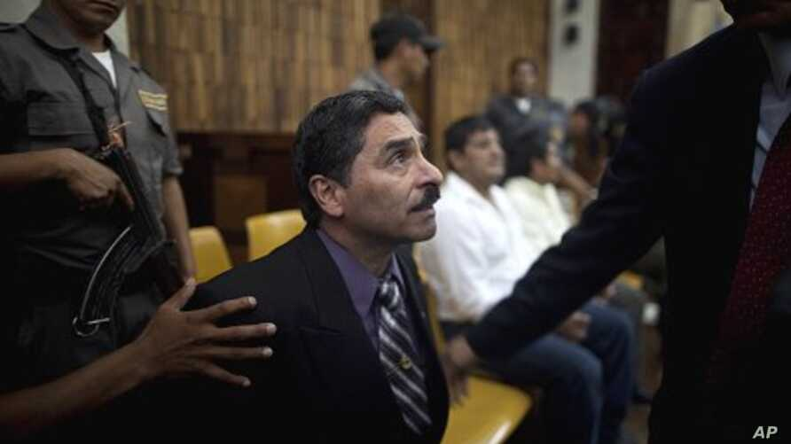 Former special forces soldier Carlos Antonio Carias, center, gestures to his lawyer after being sentenced at the end of his trial in Guatemala City, Tuesday, Aug. 2, 2011