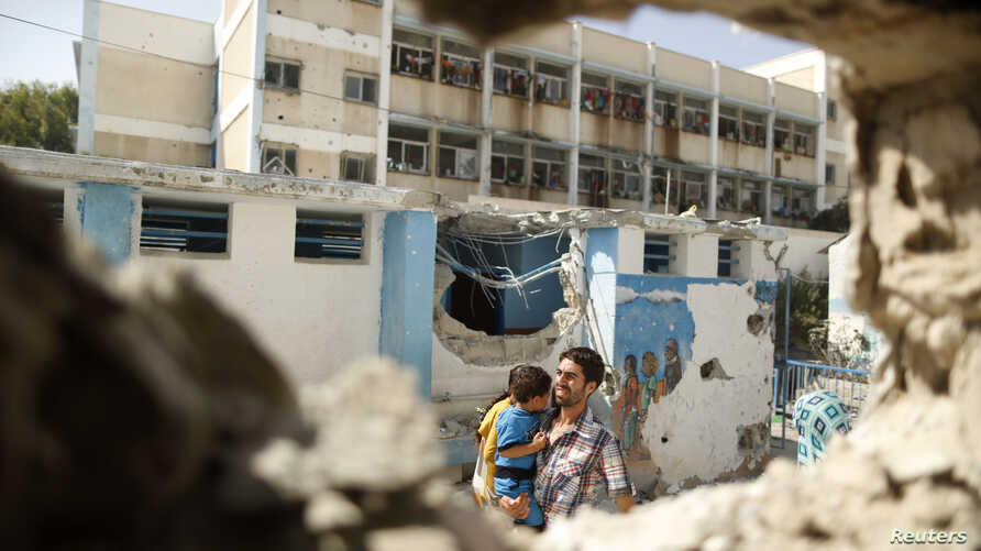 A Palestinian man pictured through a damaged classroom carries a boy at a United Nations-run school sheltering Palestinians displaced by an Israeli ground offensive, that witnesses said was hit by Israeli shelling, in Jebalya refugee camp in the nort