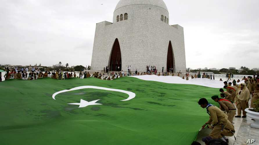 Students hold a giant representation of a Pakistani flag to celebrate the 68th Independence Day at the mausoleum of  Muhammad Ali Jinnah, founder of Pakistan in Karachi, Pakistan, Thursday, Aug. 14, 2014.