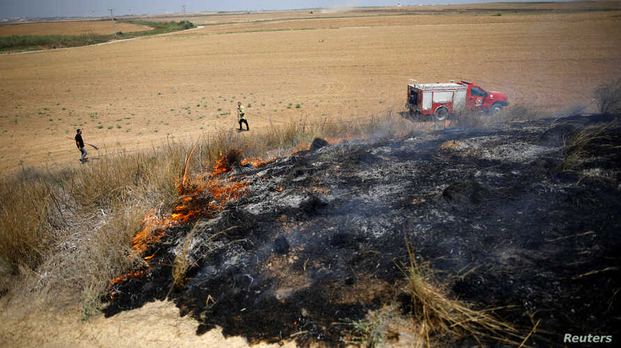Israeli firefighters attempt to extinguish fire burning scrubland in area where Palestinians have been causing blazes by flying kites and balloons loaded with flammable materials, July 20m 2018.