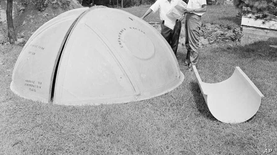 FILE - Bomb shelter manufacturer engineers Vincent Carubia, left, and Eward Klein study specifications for a fiber glass dome shelter being installed on an estate in Locust Valley, N.Y., Sept. 7, 1961.