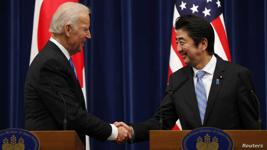 U.S. Vice President Joe Biden (L) shakes hands with Japan's Prime Minister Shinzo Abe at the end of their joint news conference following their meeting at the prime minister's official residence in Tokyo, Dec. 3, 2013. Biden urged Japan and China to