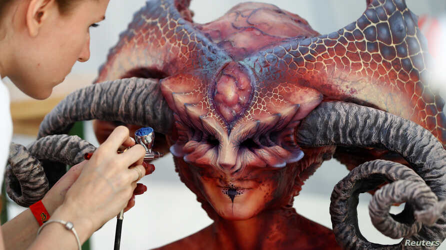 """An artist airbrushes a model during the """"World Bodypainting Festival 2017"""" in Klagenfurt, Austria, July 28, 2017."""