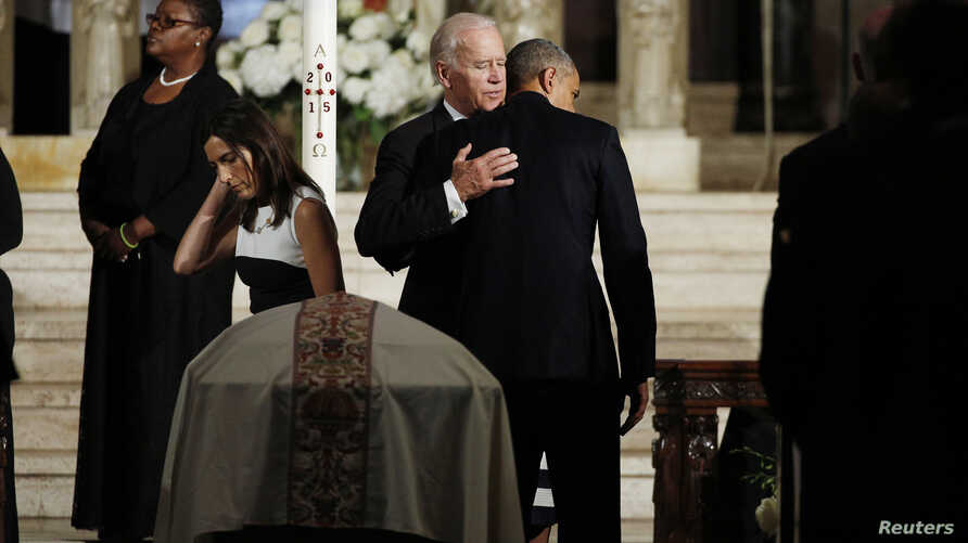 President Barack Obama, back to camera, hugs Vice President Joe Biden during the funeral of his son former Delaware Attorney General Beau Biden as Biden's widow Hallie, left, passes her husband's casket at St. Anthony of Padua church in Wilimington,