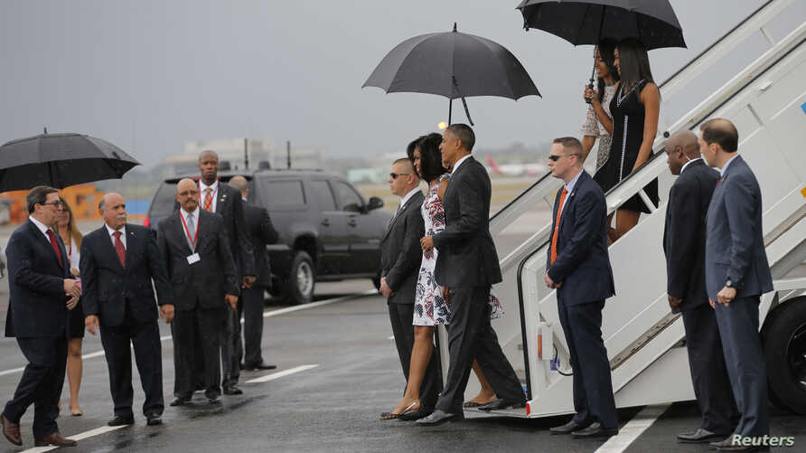 U.S. President Barack Obama and his wife Michelle approach Cuba's foreign minister Bruno Rodriguez as they arrive at Havana's international airport, March 20, 2016.
