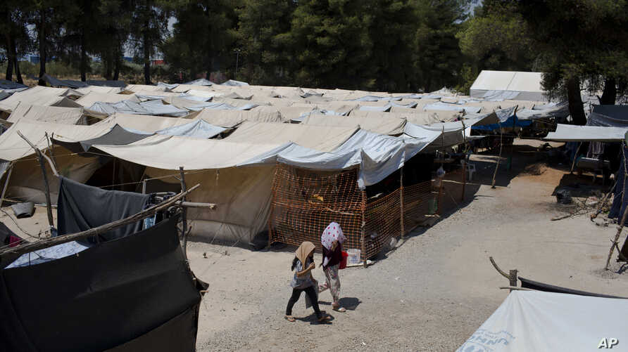 FILE - In this photo taken on Tuesday, July 14, 2016, two young girls walk among tents at Ritsona refugee camp north of Athens.