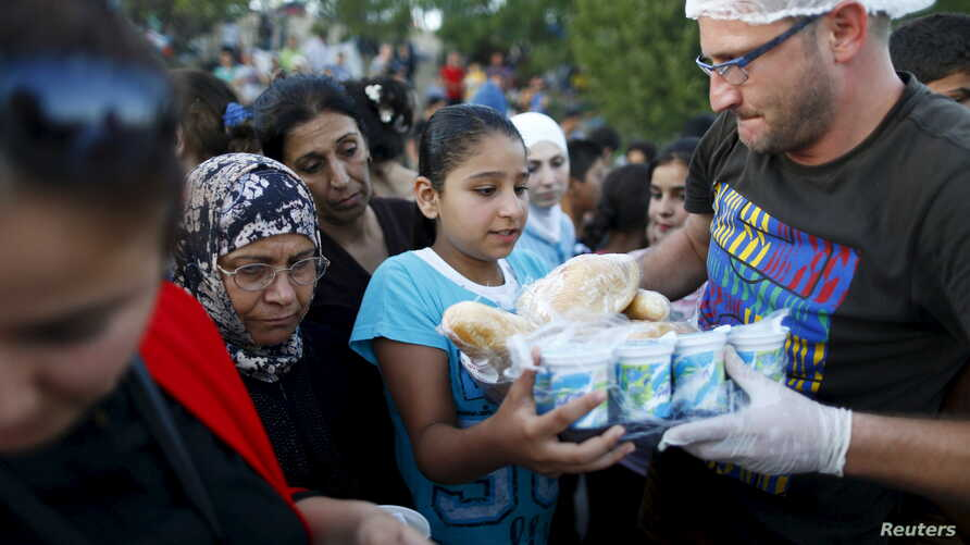 FILE - Syrian migrants queue to get food from a local NGO on the side of a highway near Edirne in Turkey, as they rest from their travel towards the Greek border, September 17, 2015.