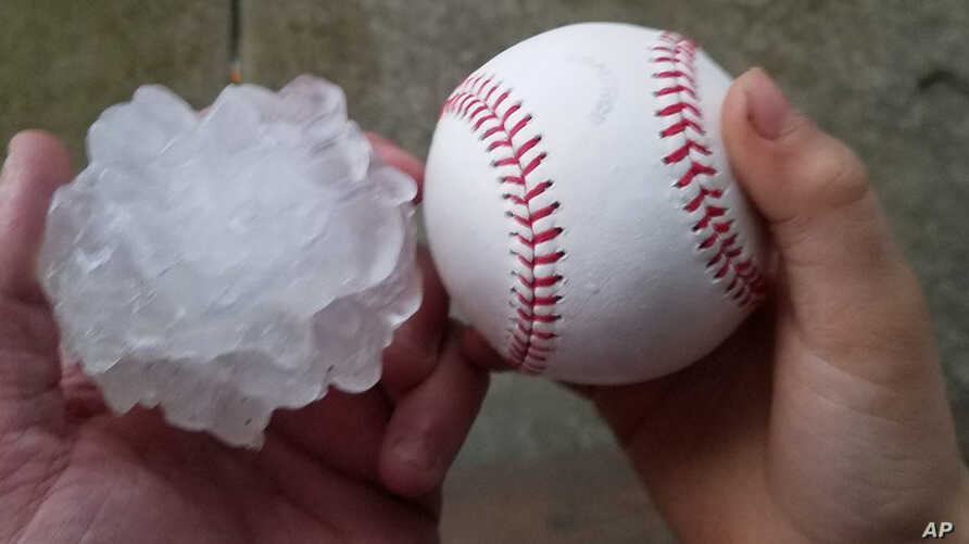 This photo provided by Tim Creedon shows his baseball and a hailstone that fell in the backyard of Creedon's home in Ottawa, Ill., Feb. 28, 2017.