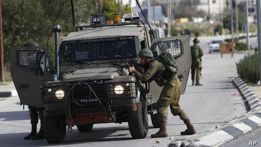 Israeli soldiers conduct a search for suspects of a shooting attack yesterday in the West Bank City of Ramallah, Dec. 10, 2018.