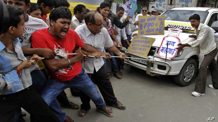 Indian people pull a car by rope and shout slogans during a protest against the price hike in diesel and capping the number of subsidized cooking gas cylinders in Ahmadabad, India, Sept. 14, 2012.