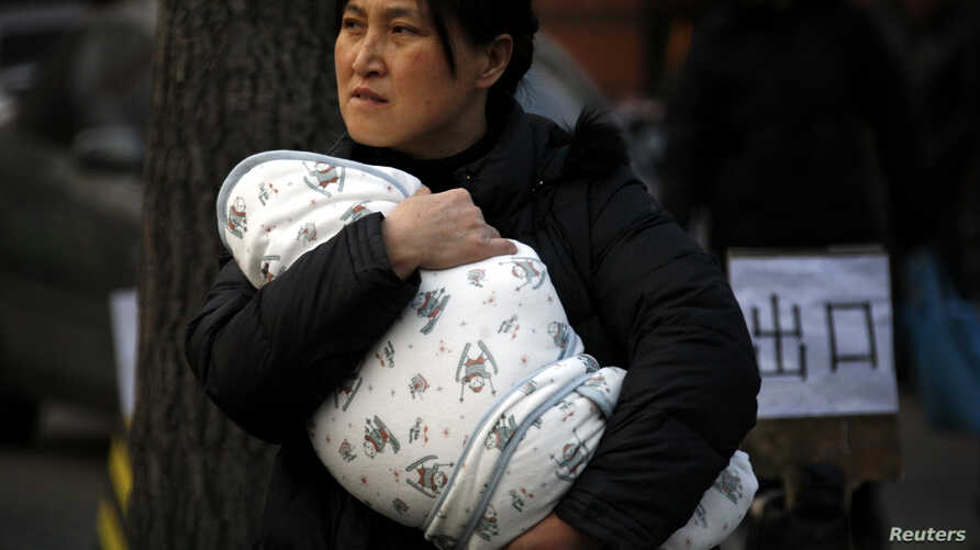 A mother carries her baby wrapped in a blanket in Beijing, (File photo).