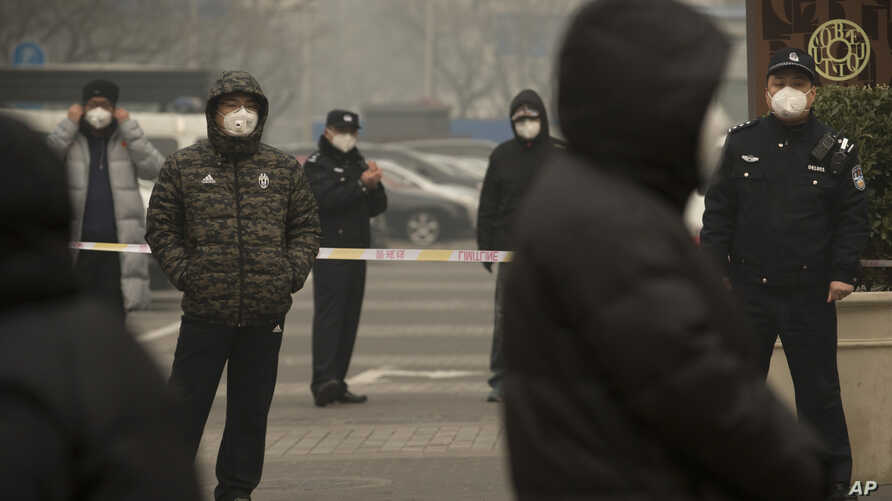 FILE - Plainclothes and uniformed police stand guard near Beijing's No. 2 People's Intermediate Court during a trial there of a human rights lawyer, in Beijing, China, Dec. 22, 2015.