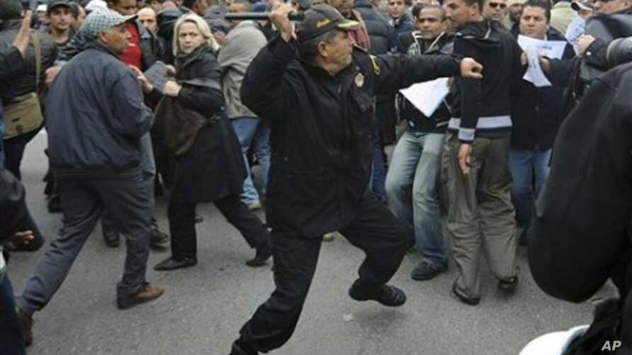 A police officer faces protesters during a demonstration against the Constitutional Democratic Rally - RCD, the party of deposed President Ben Ali, in the center of Tunis, 18 Jan 2011
