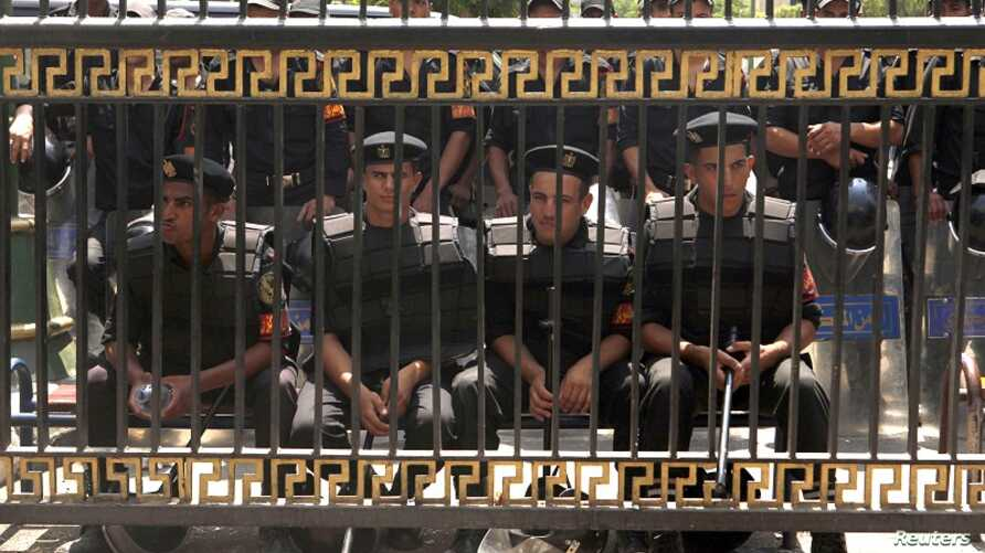 Members of the riot police stand guard in front of the parliament building in Cairo, July 10, 2012.