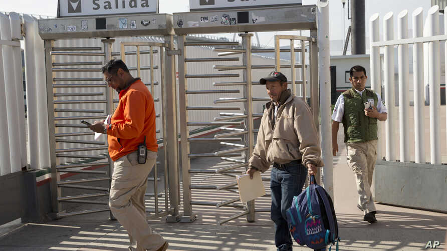 Carlos Catarldo Gomez, of Honduras, center, is escorted by Mexican officials after leaving the United States, the first person returned to Mexico to wait for his asylum trial date, in Tijuana, Mexico, Jan. 29, 2019.