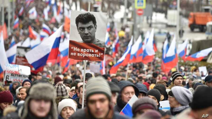 "Demonstrators, with Russian flags and a portrait of Boris Nemtsov with the words reading ""Do not lie, do not steal"", march in memory of opposition leader Boris Nemtsov in Moscow, Russia, Sunday, Feb. 24, 2019."