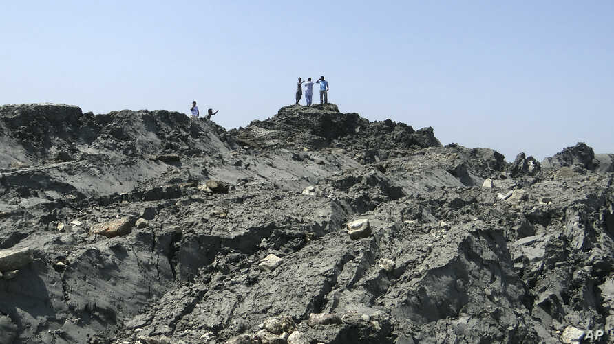In this photo released by the Gwadar local government office on Wednesday, Sept 25, 2013, people walk on an island that reportedly emerged off the Gwadar coastline in the Arabian Sea. A deadly magnitude 7.7 earthquake struck in the remote district of